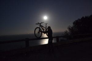 Ospite del nostro bike hotel che alza la bici verso il mare a pesaro