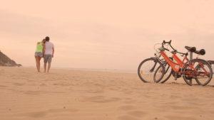 Due persone e due biciclette sulla spiaggia